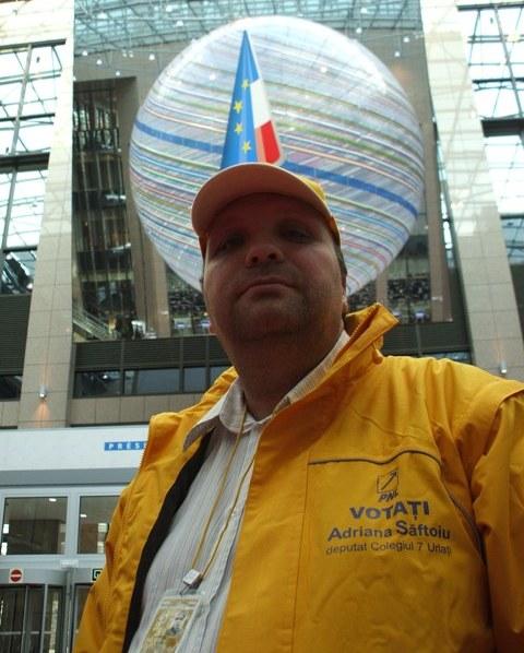 Cristian Oprea, la Consiliul Europei, Bruxelles, imbracat cu geaca si sapca inscriptionate cu sloganul electoral al Adriane Saftoiu